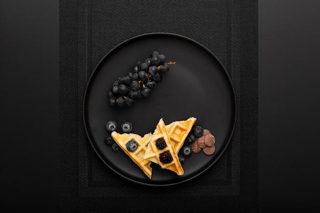 Plato oscuro con gofres y uvas sobre un paño oscuro