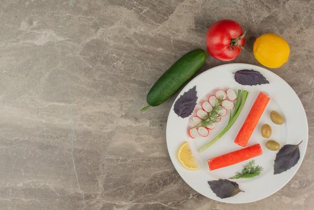 Plato de palitos de cangrejo, tomate, pepino y limón.