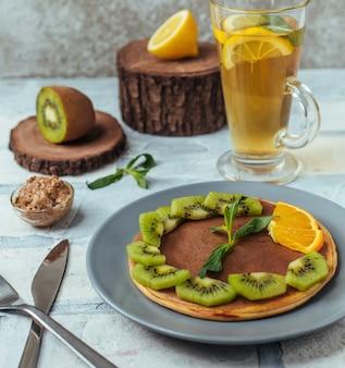Plato de panqueque con chocolate para untar y kiwi, rebanadas de ornage