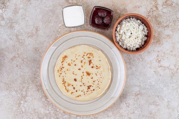 Un plato de panqueques roll con crema agria y mermelada de fresa