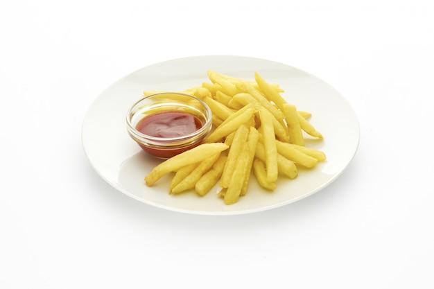 Plato de papas fritas con salsa de tomate sobre fondo blanco.