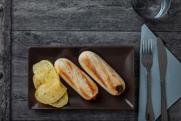 Plato de papas y sándwiches en plato marrón, junto al tenedor, vaso y servilleta