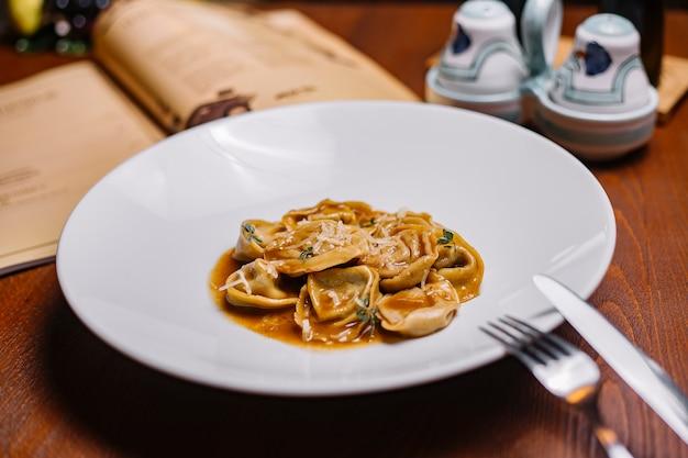Un plato de pasta de albóndigas italianas con salsa adornada con parmesano