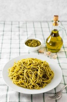 Plato de pasta con botella de aceite de oliva