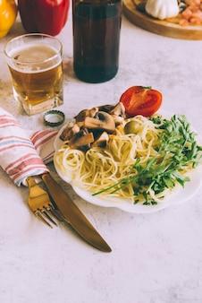 Plato de pasta delicioso con tenedor y cuchillo