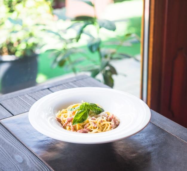 Plato de pasta de espaguetis con hojas de albahaca sobre mantel sobre la mesa