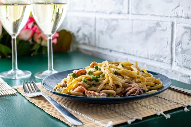 Un plato de pasta con mariscos en una mesa verde, junto a una copa de vino blanco y cubiertos en el stand de la abuela