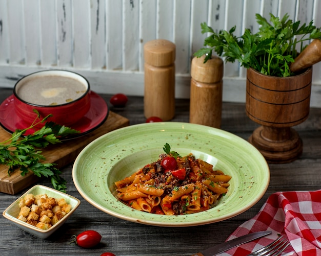 Plato de pasta penne con salsa de tomate, parmesano y hierbas