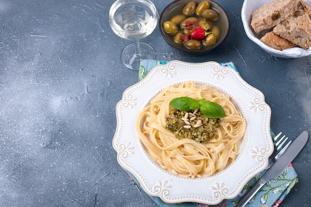 Plato con pasta con salsa de pesto y aceitunas sobre un fondo de piedra