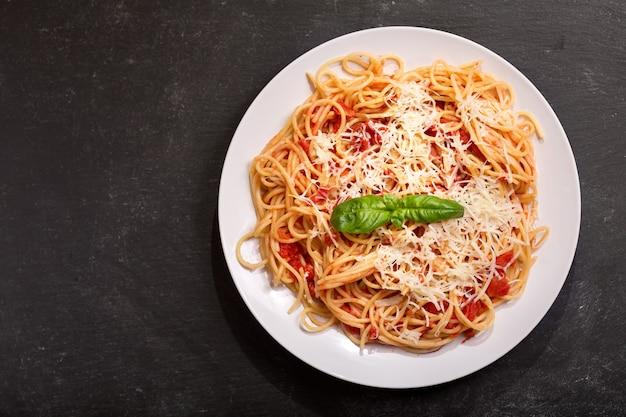 Plato de pasta con salsa de tomate y parmesano sobre fondo oscuro, vista superior