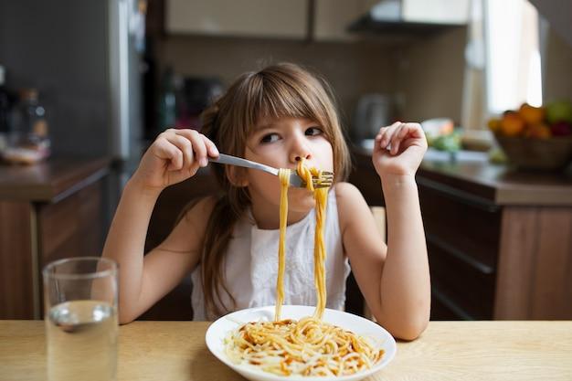Plato de pasta servido a niña juguetona