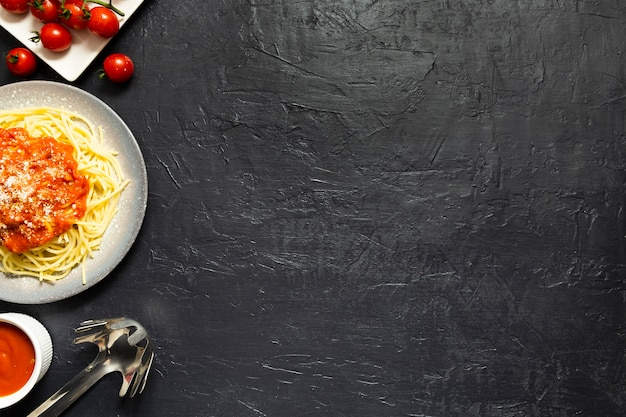 Plato de pasta con tomates en pizarra