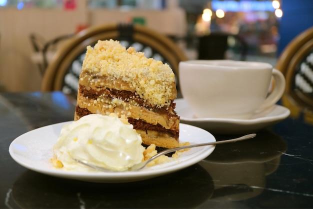 Plato de pastel de pastel de banoffee y crema batida con taza de café borrosa