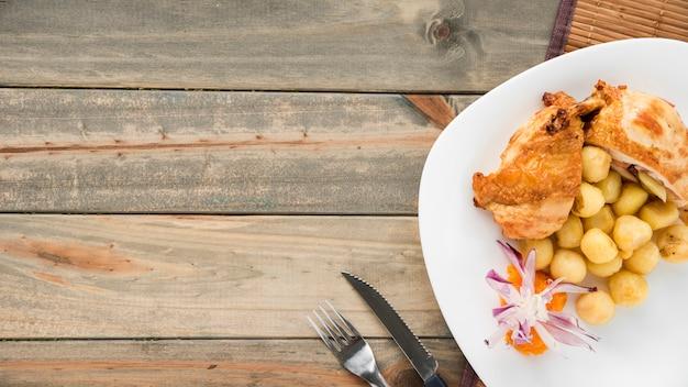Plato con pechuga de pollo y ñoquis en mesa de madera