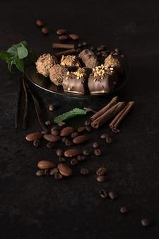 Plato pequeño lleno de caramelos de chocolate negro hechos a mano decorados con nueces, canela, menta y café
