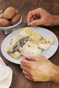 Plato con pescado hervido y mans mano