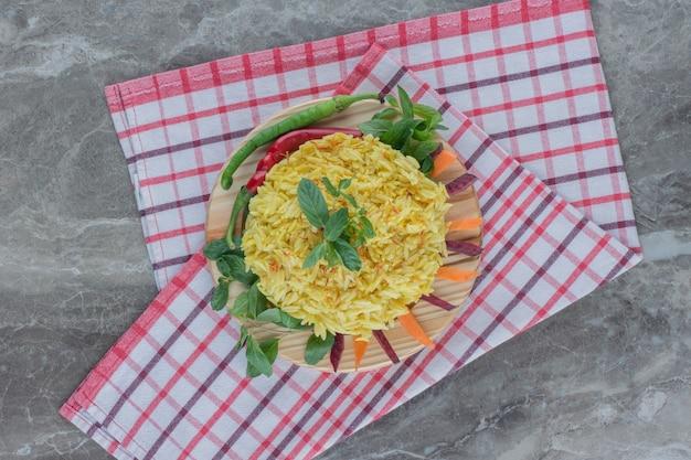 Plato de pilau sobre una toalla doblada, adornado con pimiento, hojas de menta, zanahorias en rodajas y remolacha sobre mármol.