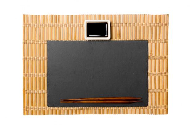 Plato de pizarra negro rectangular vacío con palillos para sushi y salsa de soja sobre estera de bambú amarillo. vista superior con copyspace