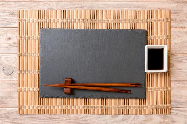 Plato de pizarra negro rectangular vacío con palillos para sushi y salsa de soja sobre madera