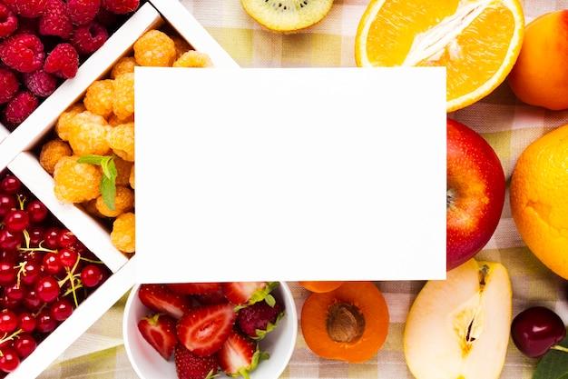Plato plano de bayas frescas y frutas con papel.