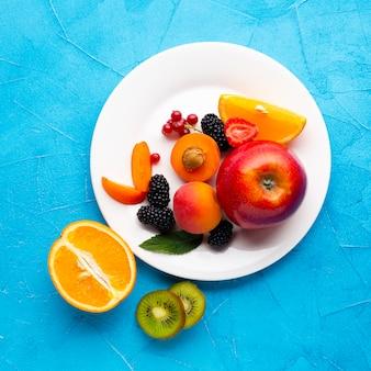 Plato plano de frutas y bayas frescas.