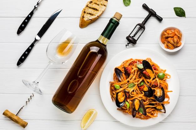 Plato plano de mejillones, pasta y vino.