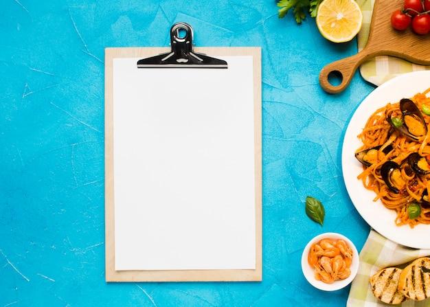 Plato plano de pasta de mejillones con portapapeles