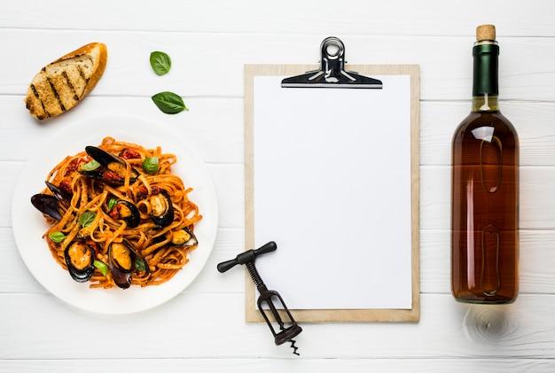 Plato plano de pasta de mejillones y vino con portapapeles.