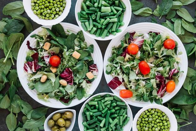 Plato plano de platos con ensaladas y judías verdes