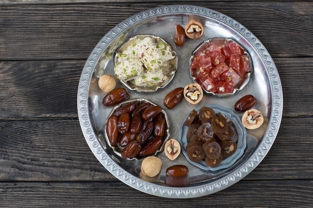 En un plato de plata dátiles, baklava con nueces, halva, delicias turcas.