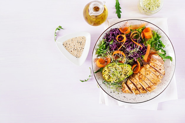 Plato de plato de buda con filete de pollo, aguacate, col roja, zanahoria, ensalada de lechuga fresca y sésamo.