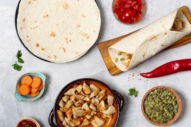 Plato de pollo, burrito y tortilla cerca de verduras en la mesa