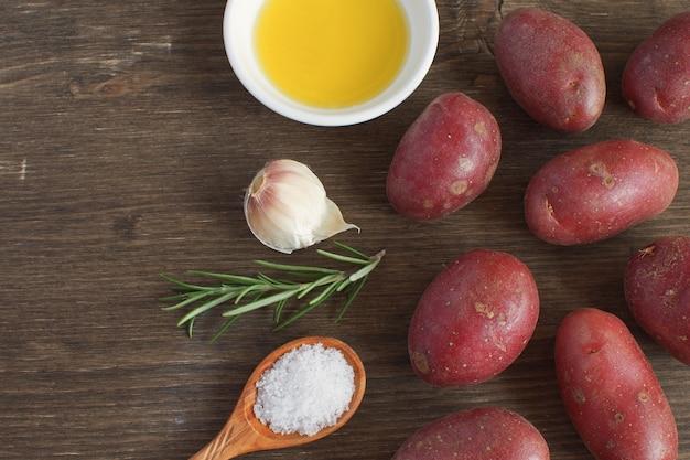 Plato de porcelana de aceite de oliva rama de romero mezcla de pimienta ajo condimento especias patata cruda