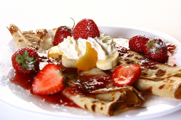 Plato de postre con panqueques y fresa
