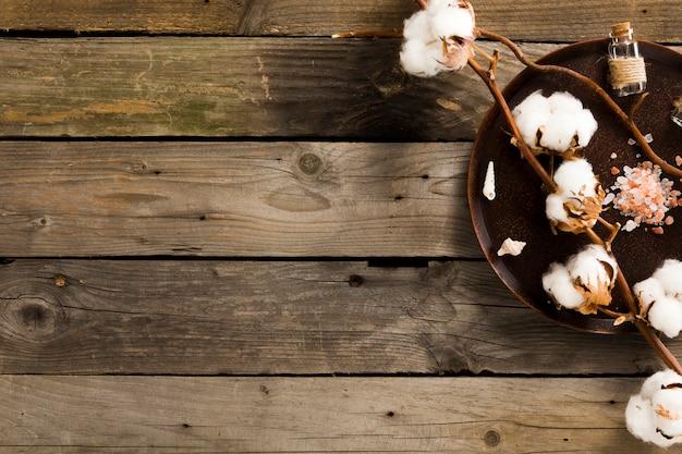 Plato con productos de spa y flores de algodón en la mesa