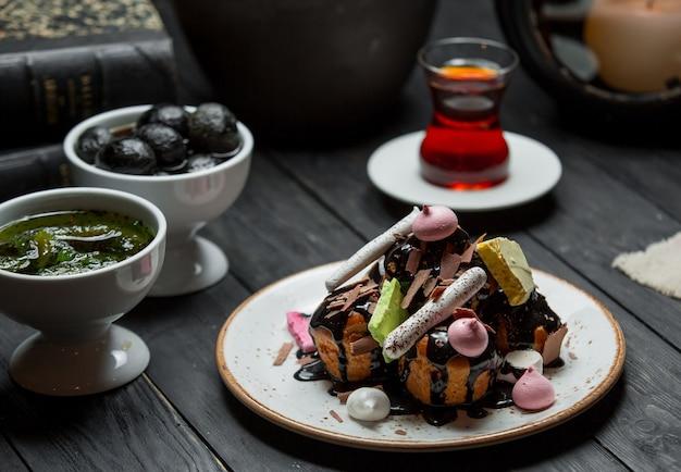 Un plato de profiteroles servido con salsa de chocolate.