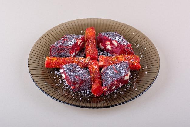 Plato de pulpas de frutas confitadas colocado sobre fondo blanco. foto de alta calidad