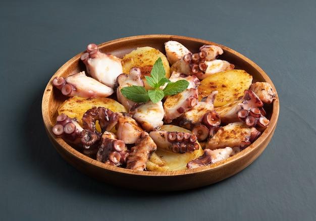Plato de pulpo cocido servido con patatas cocidas en rodajas, pimentón ahumado y aceite de oliva. en mesa rústica