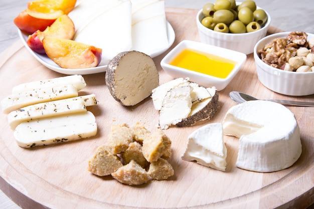 Plato de queso. 4 tipos de queso, melón, nectarina, nueces, aceitunas. de cerca. enfoque selectivo.