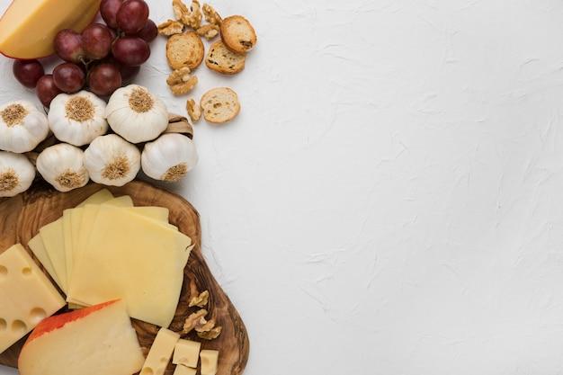 Plato de queso con bulbo de ajo; uvas rojas; pan y nuez contra fondo concreto