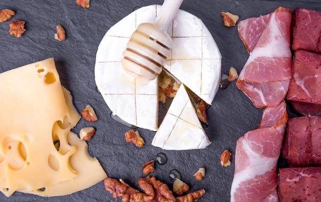 Plato de queso y carne con nueces en placa de pizarra negra. vista superior. camembert con miel