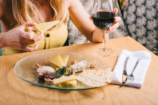 Plato con queso. chica sosteniendo vaso de vino tinto en el fondo. deliciosa mezcla de queso con nueces, miel. plato de degustación en un plato. comida por vino.