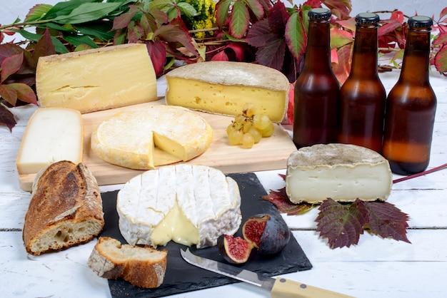 Plato de queso francés con botellas de cerveza.