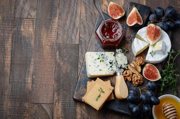 Plato de queso con frutas y nueces.