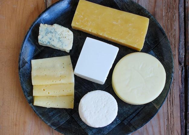 Plato de queso rústico con diferentes quesos y uvas