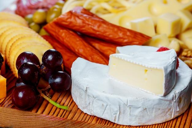 Plato de queso servido con galletas, quesos surtidos.