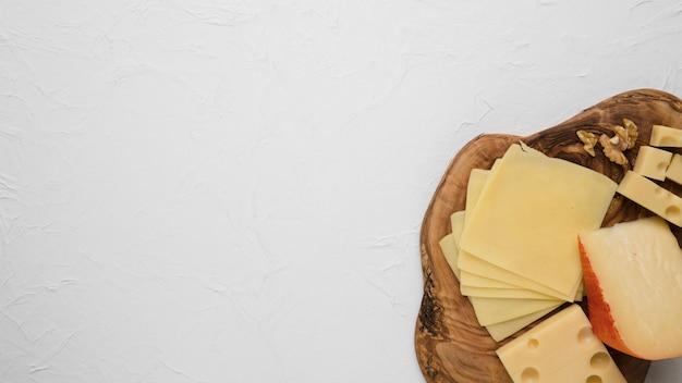Plato de queso servido con nuez aislado en blanco
