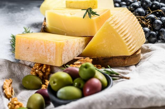 Plato de queso servido con uvas, galletas, aceitunas y nueces. surtido de deliciosos aperitivos. fondo gris vista superior