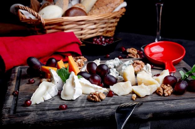 Plato de queso servido con uvas, miel y nueces sobre una mesa de madera. varios tipos de queso
