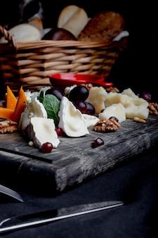 Plato de queso servido con uvas, miel y nueces.